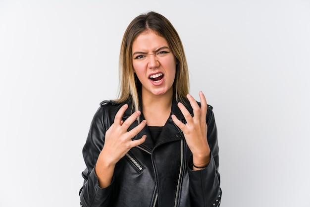 Młoda kaukaski kobieta ubrana w czarną skórzaną kurtkę zdenerwowany krzyczy z napiętymi rękami.