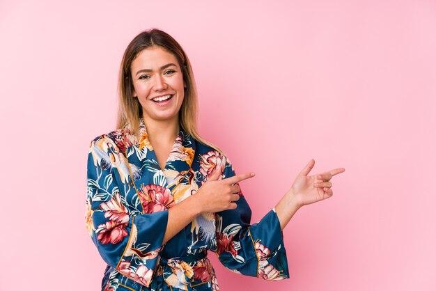 Młoda kaukaski kobieta ubrana w piżamę podekscytowany, wskazując palcami wskazującymi z dala.