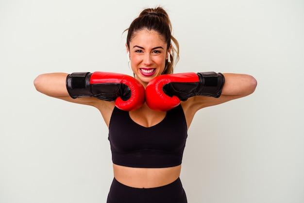 Młoda kaukaski kobieta walczy z rękawic bokserskich na białym tle na białej ścianie