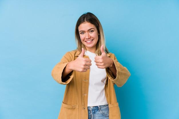 Młoda kaukaski kobieta z kciukami w górę, wiwatuje, wspiera i szanuje koncepcję.