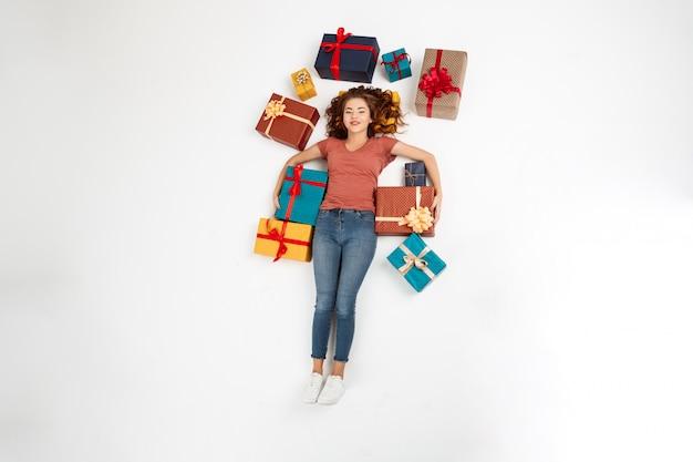 Młoda kędzierzawa kobieta kłama na podłoga wśród prezentów pudełek