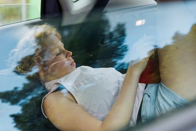 Młoda kędzierzawa kobieta odpoczywa podczas gdy kłamający w samochodzie