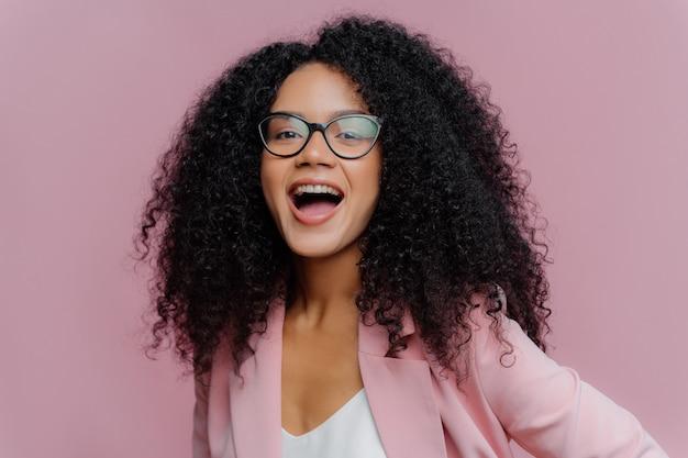 Młoda kędzierzawa kobieta otwiera usta w okularach optycznych i formalnym garniturze