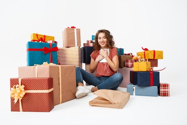 Młoda kędzierzawa kobieta siedzi na podłoga wśród prezentów z właśnie otwierającą teraźniejszą pastylką