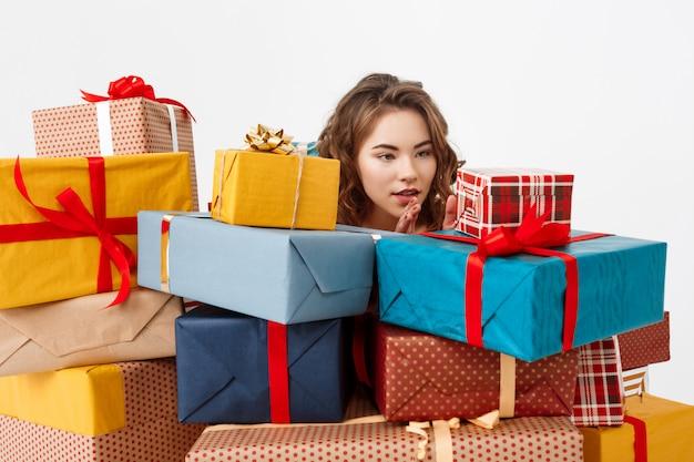 Młoda kędzierzawa kobieta wśród prezentów pudełek