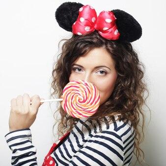 Młoda kędzierzawa kobieta z uszami myszy trzyma lizaka