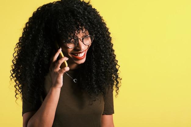 Młoda kędzierzawa z włosami afro amerykańska kobieta używa jej telefon