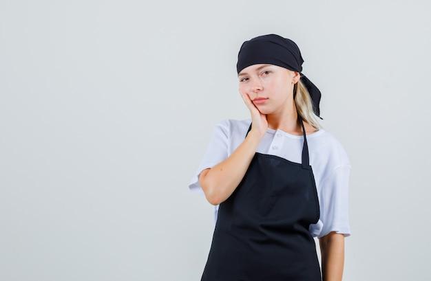 Młoda kelnerka ma ból zęba w mundurze i fartuchu i wygląda na smutną