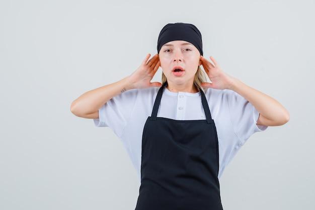 Młoda kelnerka opierająca palce na uszach w mundurze i fartuchu i wyglądająca na zirytowaną