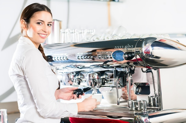 Młoda kelnerka patrząc na kamery podczas korzystania z automatycznego ekspresu do kawy