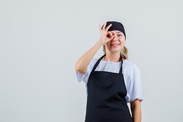 Młoda kelnerka pokazuje ok gest na oko w mundurze i fartuchu i wygląda radośnie