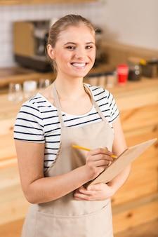 Młoda kelnerka. pozytywnie miła zachwycona kobieta uśmiecha się do ciebie i robi notatki podczas pracy jako kelnerka