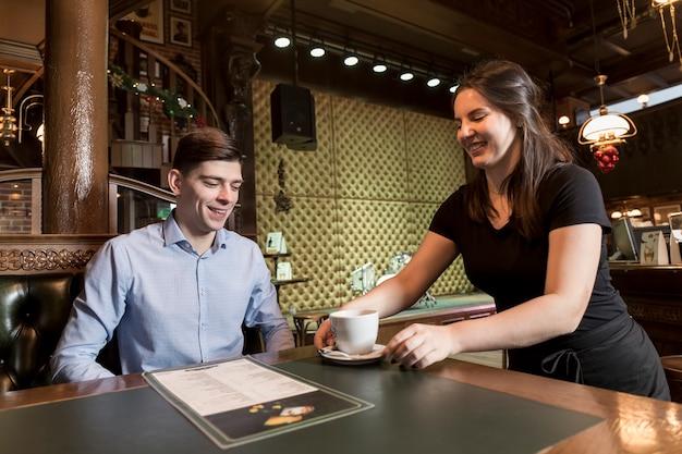 Młoda kelnerka serwuje kawę do klienta