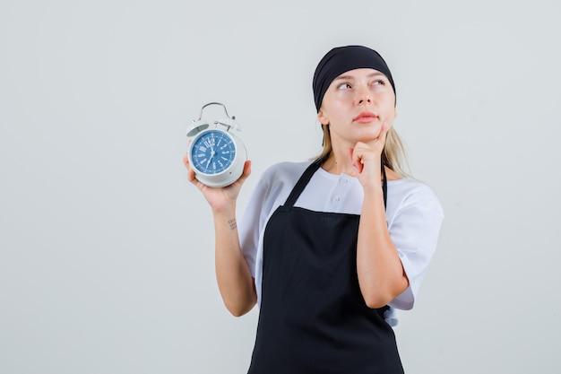 Młoda kelnerka trzyma budzik w mundurze i fartuchu i wygląda zamyślona