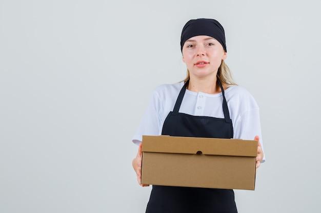 Młoda kelnerka trzyma karton w mundurze i fartuchu
