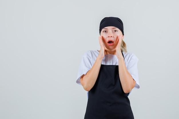 Młoda kelnerka trzymając się za ręce w pobliżu ust w mundurze i fartuchu