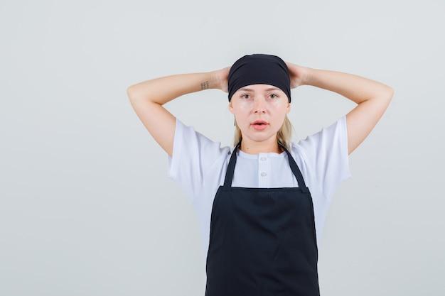 Młoda kelnerka trzymając się za ręce za głową w mundurze i fartuchu