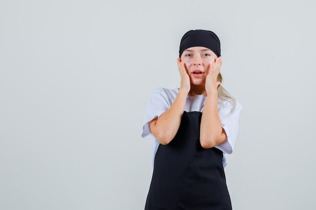 Młoda kelnerka trzymająca się za ręce na policzkach w mundurze i fartuchu i wyglądająca na zdumioną