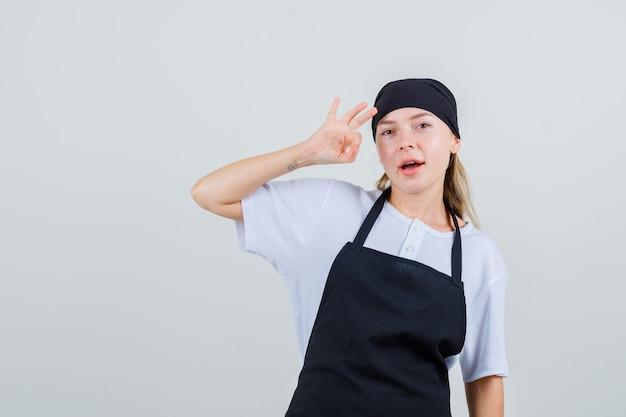 Młoda kelnerka w mundurze i fartuchu pokazuje znak ok i wygląda na zadowoloną