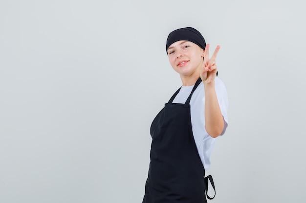 Młoda kelnerka w mundurze i fartuchu pokazuje znak zwycięstwa i wygląda wesoło