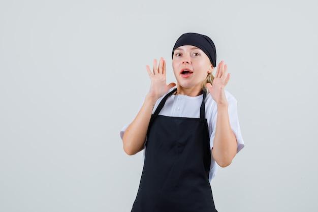 Młoda kelnerka w mundurze i fartuchu prewencyjnie podnosi ręce i wygląda na przestraszoną