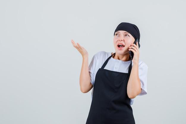 Młoda kelnerka w mundurze i fartuchu rozmawia przez telefon komórkowy i wygląda na zdumioną
