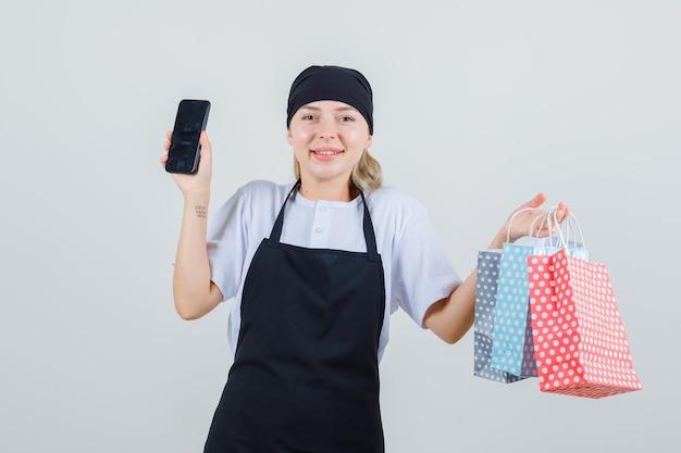 Młoda kelnerka w mundurze i fartuchu trzyma papierowe torby i telefon komórkowy i wygląda wesoło