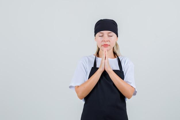 Młoda kelnerka w mundurze, trzymając się za ręce w geście modlitwy i wyglądająca na spokojną
