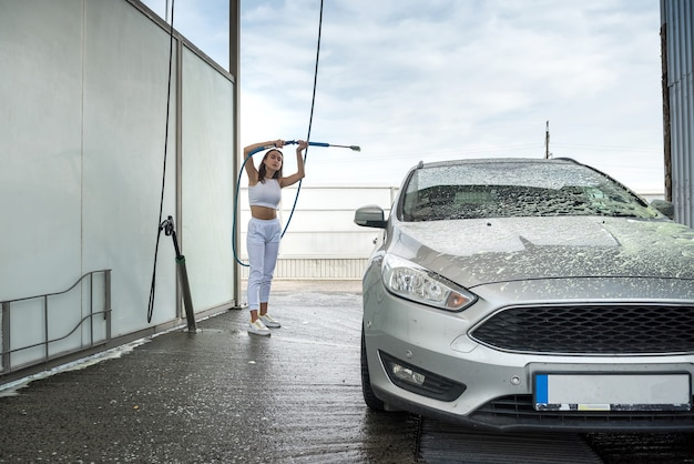 Młoda kierowca z węża wysokociśnieniowego nakłada pianę mydlaną na samochód do czyszczenia z brudu w ręcznej myjni samochodowej
