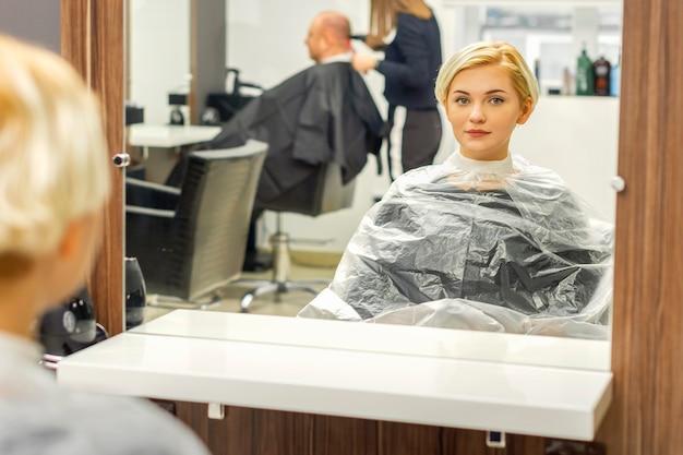 Młoda klientka czeka na fryzjera, patrząc w lustro w salonie fryzjerskim