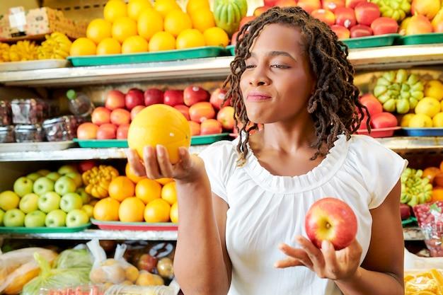 Młoda klientka trzymająca w dłoniach owoce i wybierająca te dojrzałe podczas zakupów w sklepie