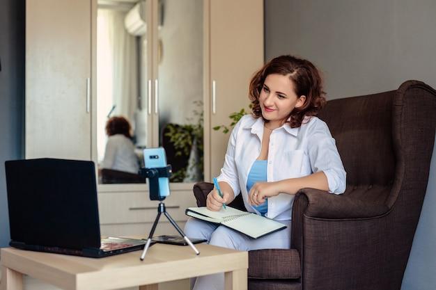 Młoda kobieta 30 lat w białej koszuli pracuje w domowym biurze i prowadzi konferencję szkoleniową za pomocą połączeń wideo, telefon jest na statywie