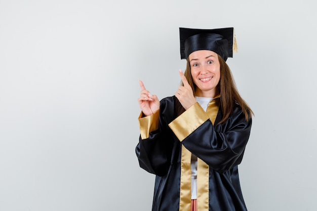 Młoda kobieta absolwentka skierowana w górę w akademickim stroju i wesoły wyglądający. przedni widok.