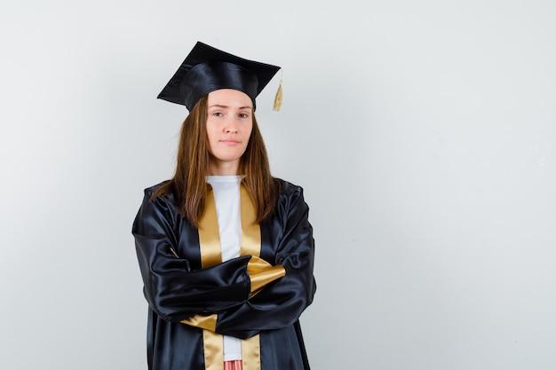 Młoda kobieta absolwentka stoi ze skrzyżowanymi rękami w akademickim stroju i wygląda pewnie. przedni widok.