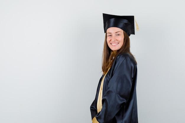 Młoda kobieta absolwentka w akademickim stroju pozowanie, stojąc i patrząc szczęśliwy, widok z przodu.