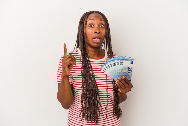Młoda kobieta african american gospodarstwa banknotów na białym tle o pomysł, koncepcja inspiracji.