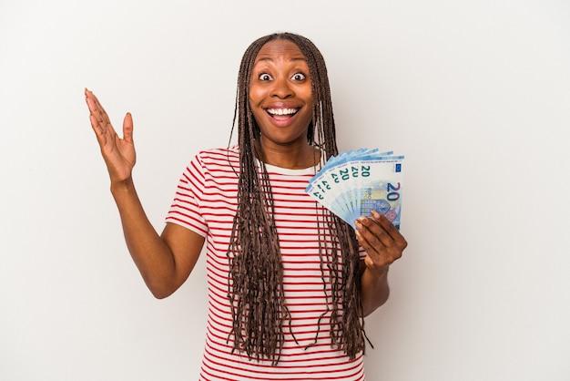 Młoda kobieta african american gospodarstwa banknotów na białym tle odbiera miłą niespodziankę, podekscytowany i podnosząc ręce.