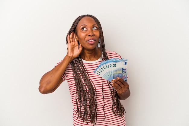 Młoda kobieta african american gospodarstwa banknotów na białym tle próbuje słuchać plotek.