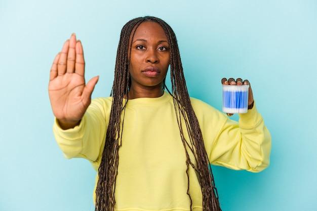 Młoda kobieta african american gospodarstwa bawełniane byki na białym tle na pąki stojący z wyciągniętą ręką pokazując znak stop, uniemożliwiając.