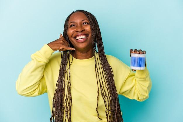 Młoda kobieta african american gospodarstwa bawełniane byki na białym tle na pąki tle pokazano gest połączenia z telefonu komórkowego palcami.