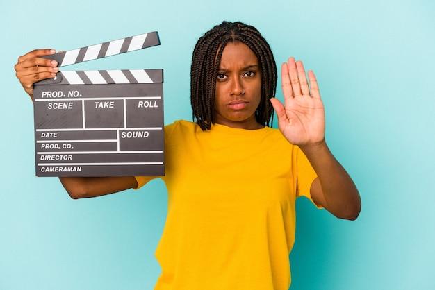 Młoda kobieta african american gospodarstwa clapperboard na białym tle na niebieskim tle stojąc z wyciągniętą ręką pokazując znak stop, uniemożliwiając.