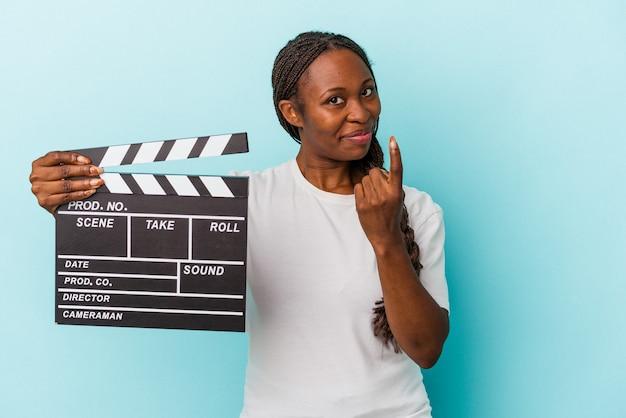 Młoda kobieta african american gospodarstwa clapperboard na białym tle na niebieskim tle wskazując palcem na ciebie, jakby zapraszając zbliżyć.