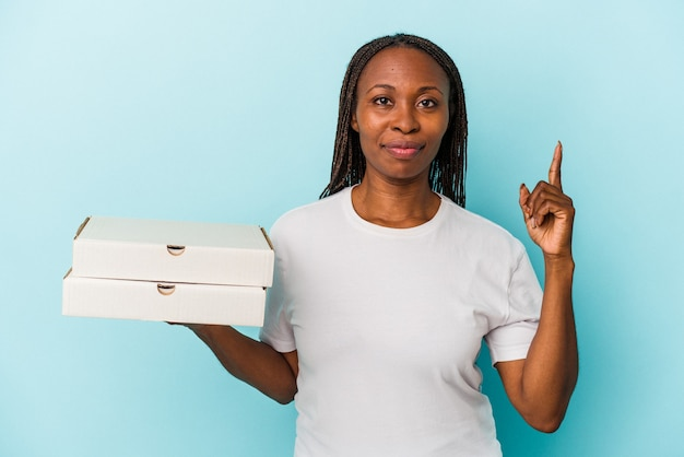 Młoda kobieta african american gospodarstwa pizze na białym tle na niebieskim tle wyświetlono numer jeden palcem.