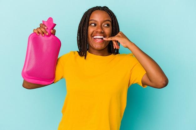 Młoda kobieta african american gospodarstwa worek gorącej wody na białym tle na niebieskim tle pokazując gest połączenia z telefonu komórkowego palcami.
