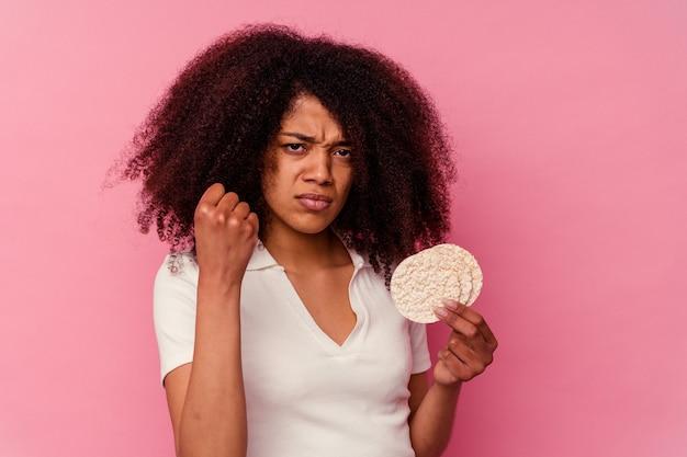 Młoda kobieta african american jedzenie ciastek ryżowych na białym tle na różowym tle pokazując pięść do aparatu, agresywny wyraz twarzy.