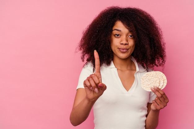Młoda kobieta african american jedzenie ciastka ryżowe na białym tle na różowym tle wyświetlono numer jeden palcem.