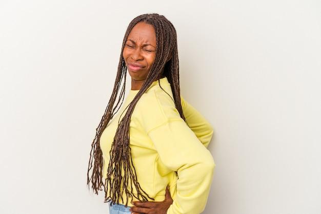 Młoda kobieta african american na białym tle cierpi na ból pleców.