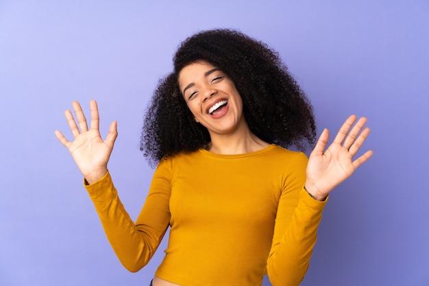 Młoda kobieta african american na białym tle licząc dziesięć palcami