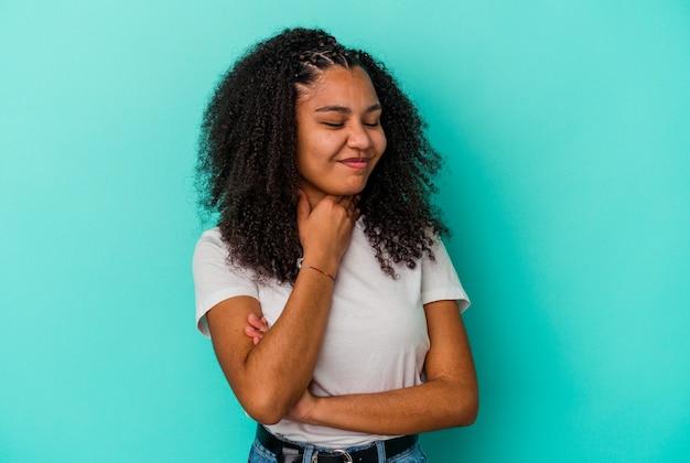 Młoda kobieta african american na białym tle na niebieskim tle cierpi na ból gardła z powodu wirusa lub infekcji.