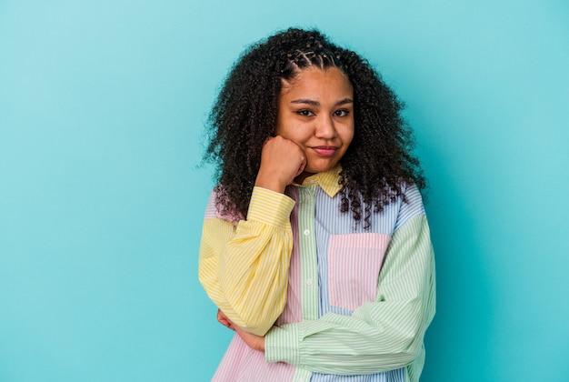 Młoda kobieta african american na białym tle na niebieskim tle, która czuje się smutna i zamyślona, patrząc na miejsce.